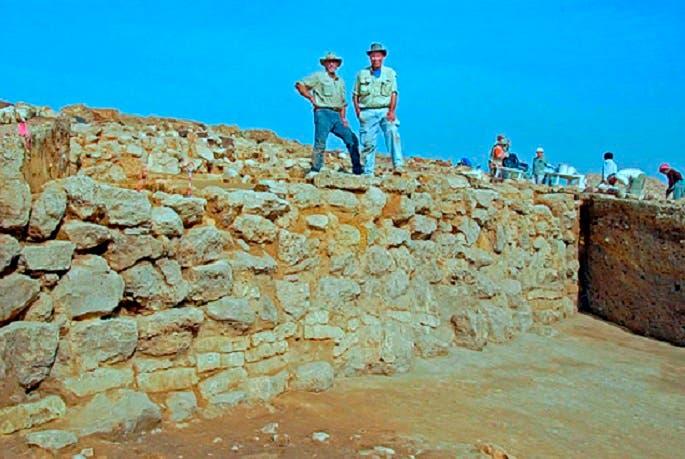 البروفيسور كوللينز، إلى اليسار، بين مما تم العثور عليه من بقايا مدينة دمرها القصاص الإلهي