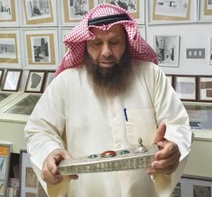 د . محمد بن إبراهيم الشيباني يعاين محبرة أثرية من مقتنيات مركز المخطوطات والتراث